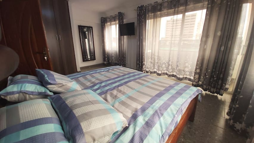 Large, roomy bedroom with large slider windows and a Cozy King Size Bed.