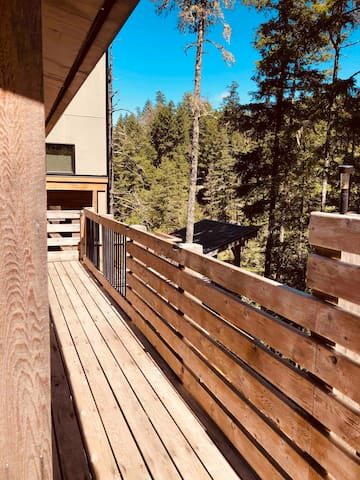 Side deck of Treehouse Cottage , the way leading towards stairs down to detached private hot tub building and to stairs down cliff to private dock
