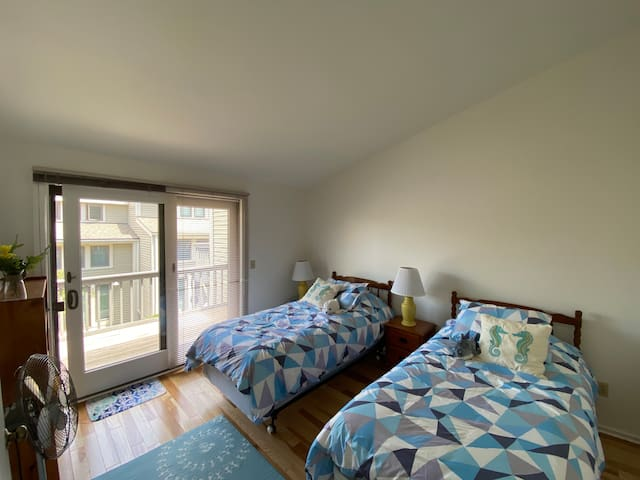Upstairs bedroom with matching twin beds and private balcony, featuring an outdoor recliner! Bedroom has 1 closet and ample storage space.