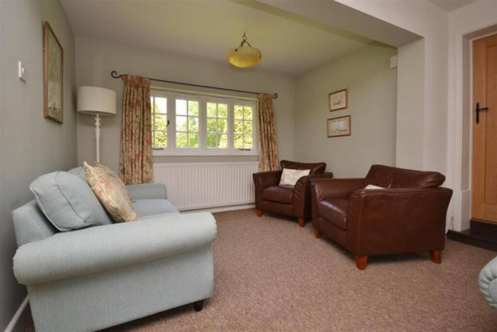 Far end of Sitting room with sofa and two chairs - view over the gardens