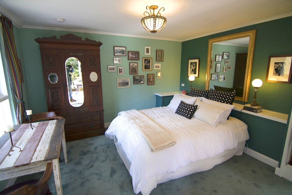 A long view of the bedroom which faces a large window looking out to the gully and garden terrace