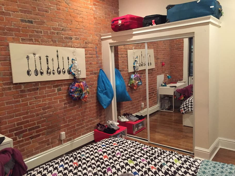 The bedroom has a huge closet with hangers and shelves.