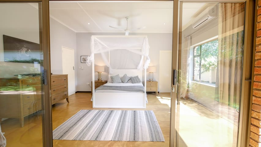 King Size Bedroom, looking in from the veranda, with en-suite bathroom, with bath and shower.  Air-conditioned.