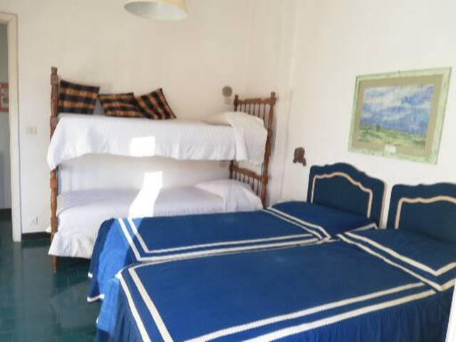 camera con quattro letti e affaccio sul terrazzino che porta al giardino