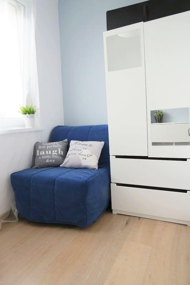 Rozkładane jednoosobowe łóżko, w trakcie dnia posłuży za wygodny fotel, a nocą zapewni spokojny sen. Pojemna szafa, która pomieści wszystkie bagaże.