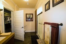 On suite bathroom with pocket door to bedroom and door to hallway.