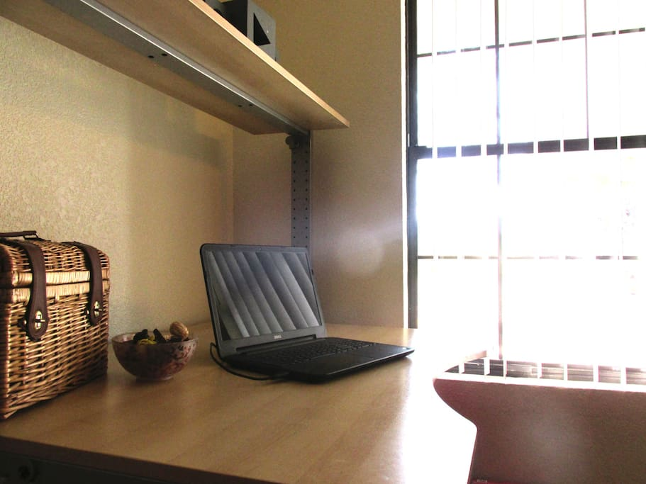 Personal desk and window with a sunny view.