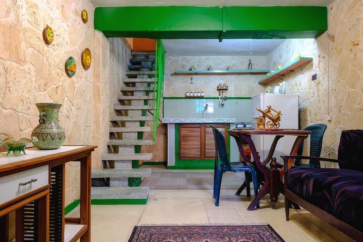 Sala de estar, cocina con hornilla de gas, refrigerador y utensilios para cocinar