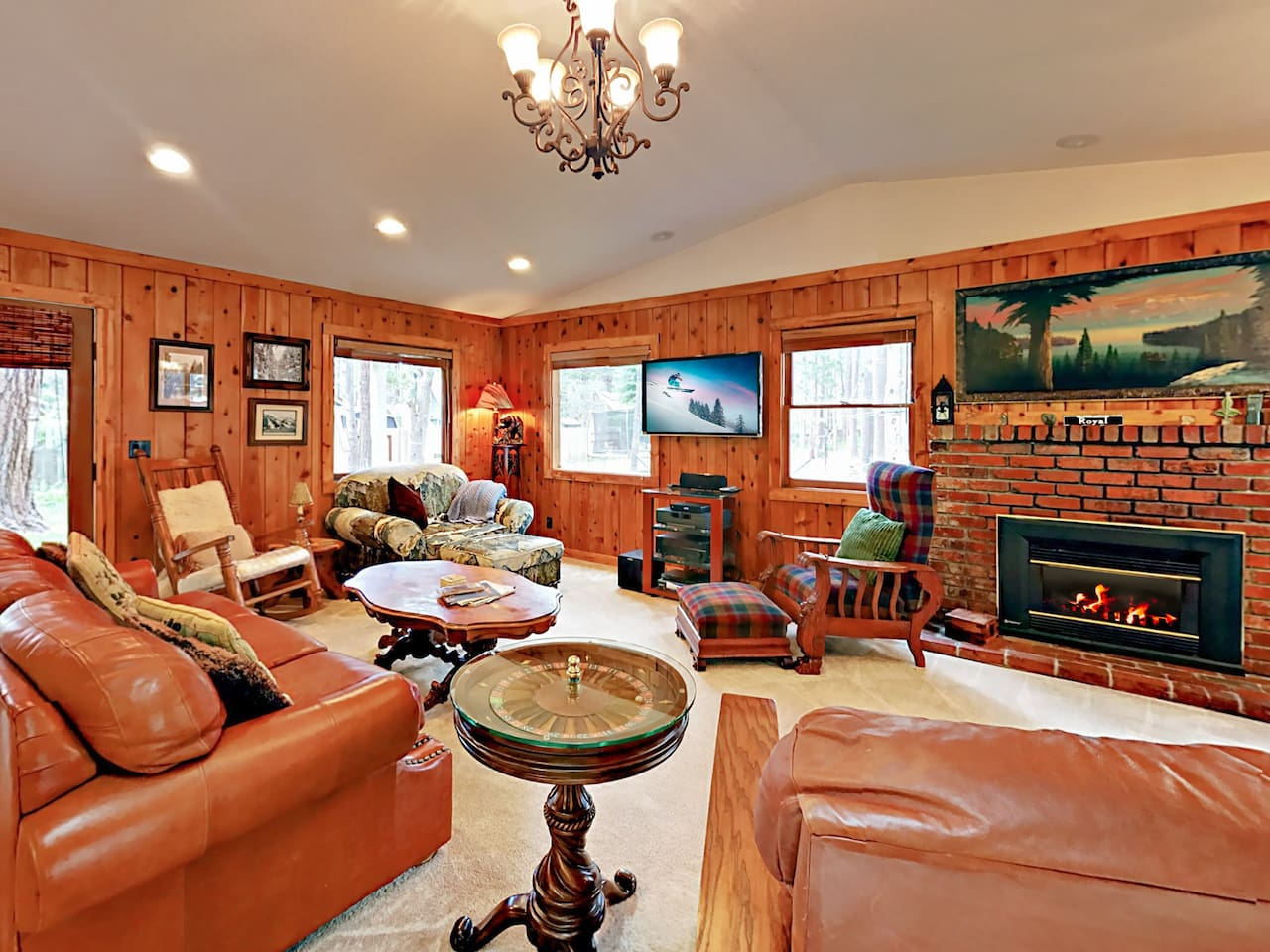Knotty pine walls, a gas fireplace, and plush leather furniture create a welcoming lodge feel.