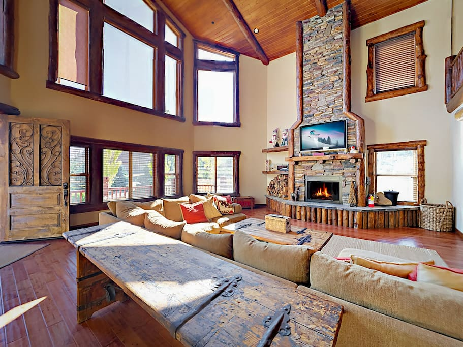 Soaring vaulted ceilings and stunning floor-to-ceiling stone fireplace create a lodge feel in the large living room