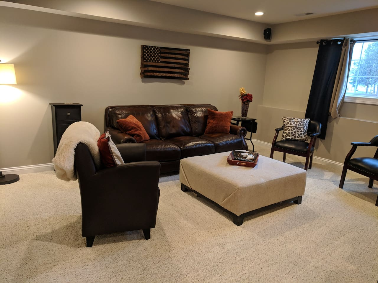 Comfy, cozy living room with a leather sofa and extra seating.