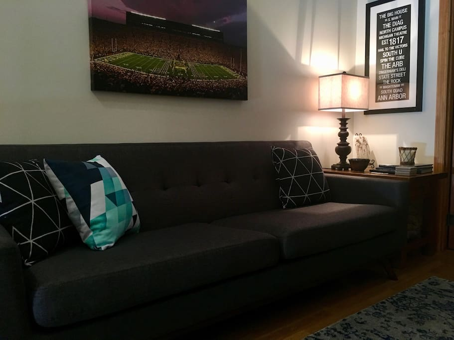 A large couch with accent pillows can sit four comfortable.