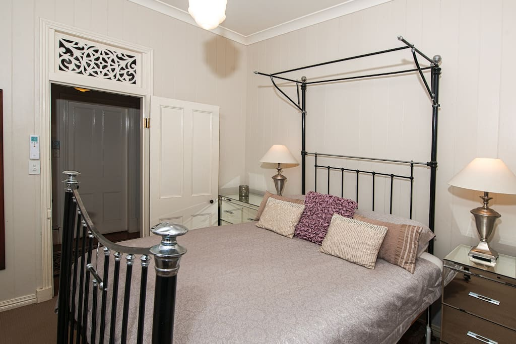 Queen size cast iron and nickel antique bed in master bedroom
