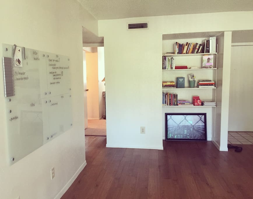 spacious living space with book shelf filled with inspiring books and dry erase 'creative' board