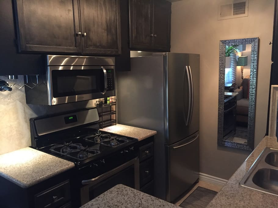 Granite countertops and stone floors with all stainless steel appliances: refrigerator, microwave, oven and dishwasher.