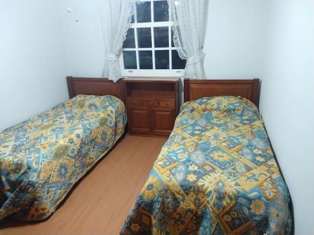 Quarto frente, duas camas de solteiro.