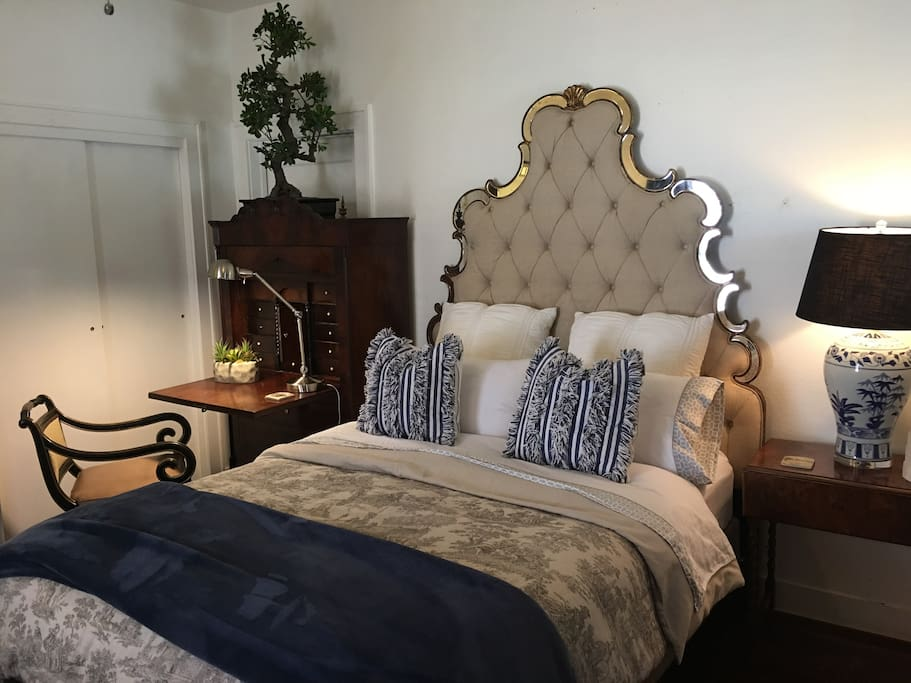 Beautiful queen size french bed with luxury linens. The bed is surrounded by a 160 year old secretary from Denmark.