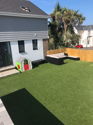 Spacious  astroturfed front garden with seating areas