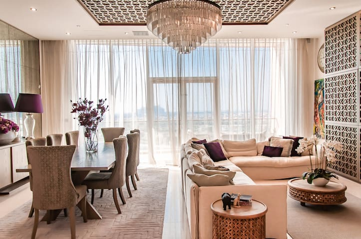 Relax and unwind on the large L shaped sofa in the living area - luxuriously decorated with many beautiful upgrades. Adjustable lighting, remote-control curtains, and walkout to large patio. Peek out the windows at the sea view & Atlantis the Palm!
