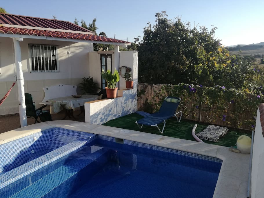 vista frontal de la casa en la que aparece piscina con yacuzzi y solarium