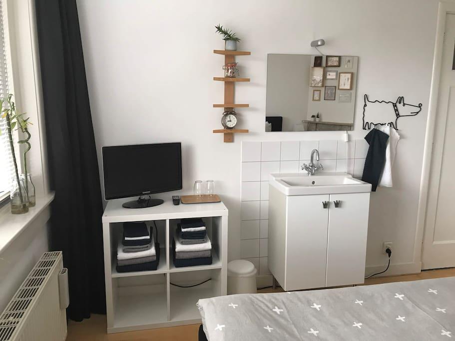 Wastafel en TV in de tweepersoonsslaapkamer