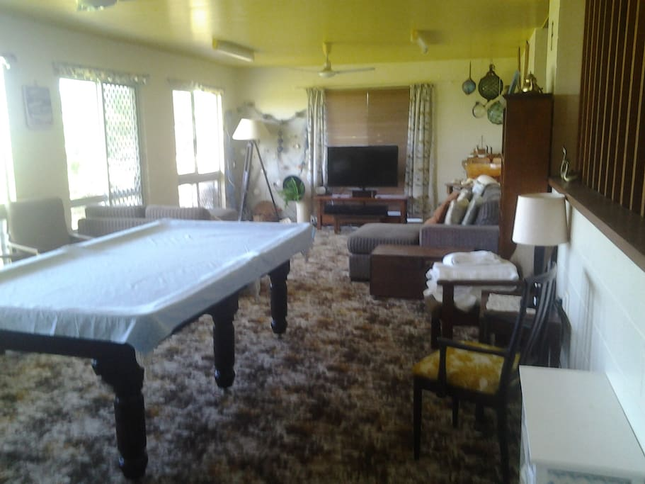 The living room with big screen TV and pool table.
