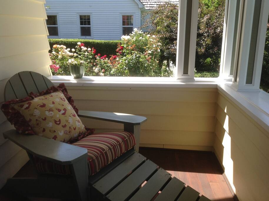 One of four Adirondack chairs on the front porch. View of the rose garden.