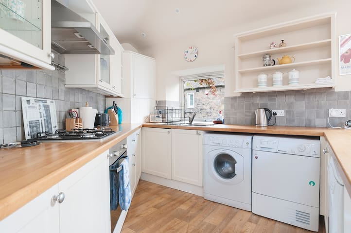 Well equipped kitchen showing washing machine and tumble dryer