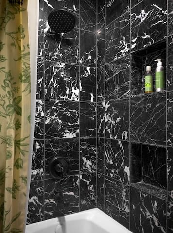 The marble shower with a rainfall shower head and tub. The shower is high enough for a tall person!
