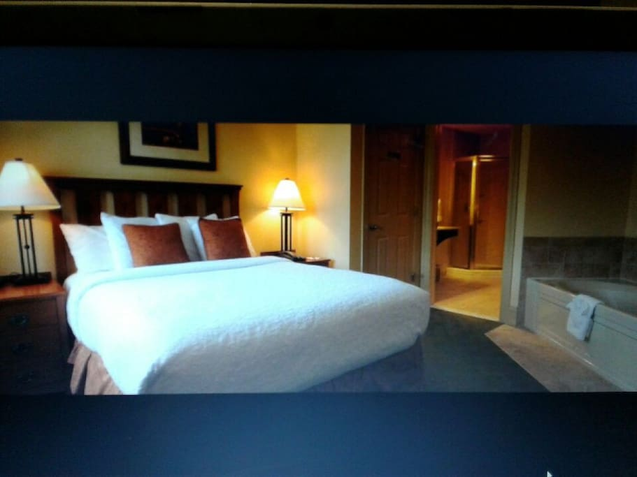 Master bedroom with jacuzzi tub,  queen sized bed and a balcony overlooking the snowtubing park