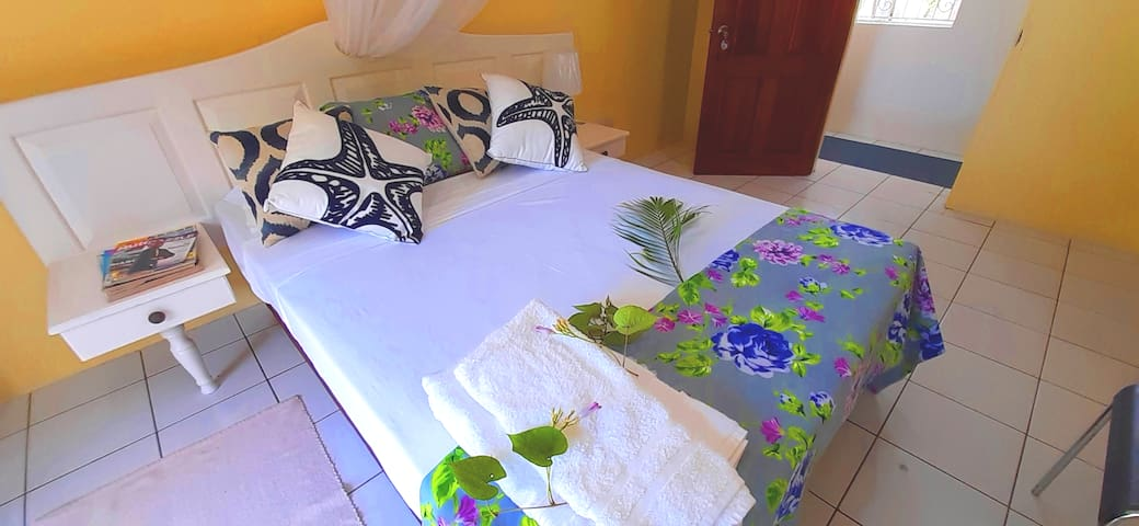 bedroom 3 with pool and garden view,  double bed, wardrobe, dresser, chair, reading lamp, mosquito net, air conditioning unit with rear access to pool