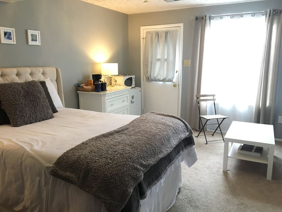 Bedroom entrance and amenities (coffee maker, snacks, microwave, fridge, wine, and water).