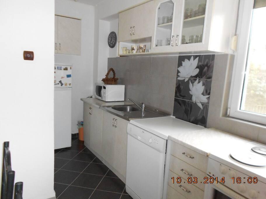 A big linear kitchen with a microvawe, big fridge, washing machine, sink and an owen.