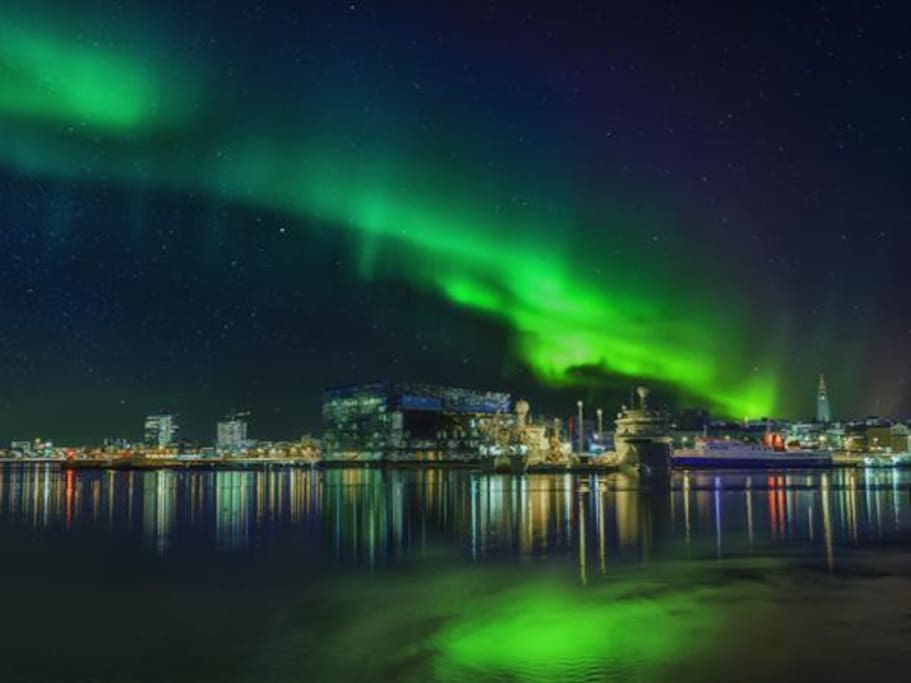 Northern lights dancing above Reykjavík city at night