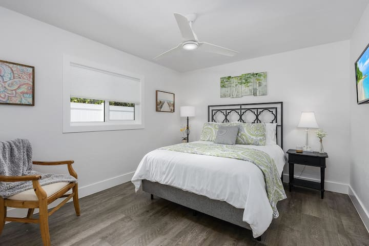 Guest bedroom with queen size bed, smart TV and closet space for storage.