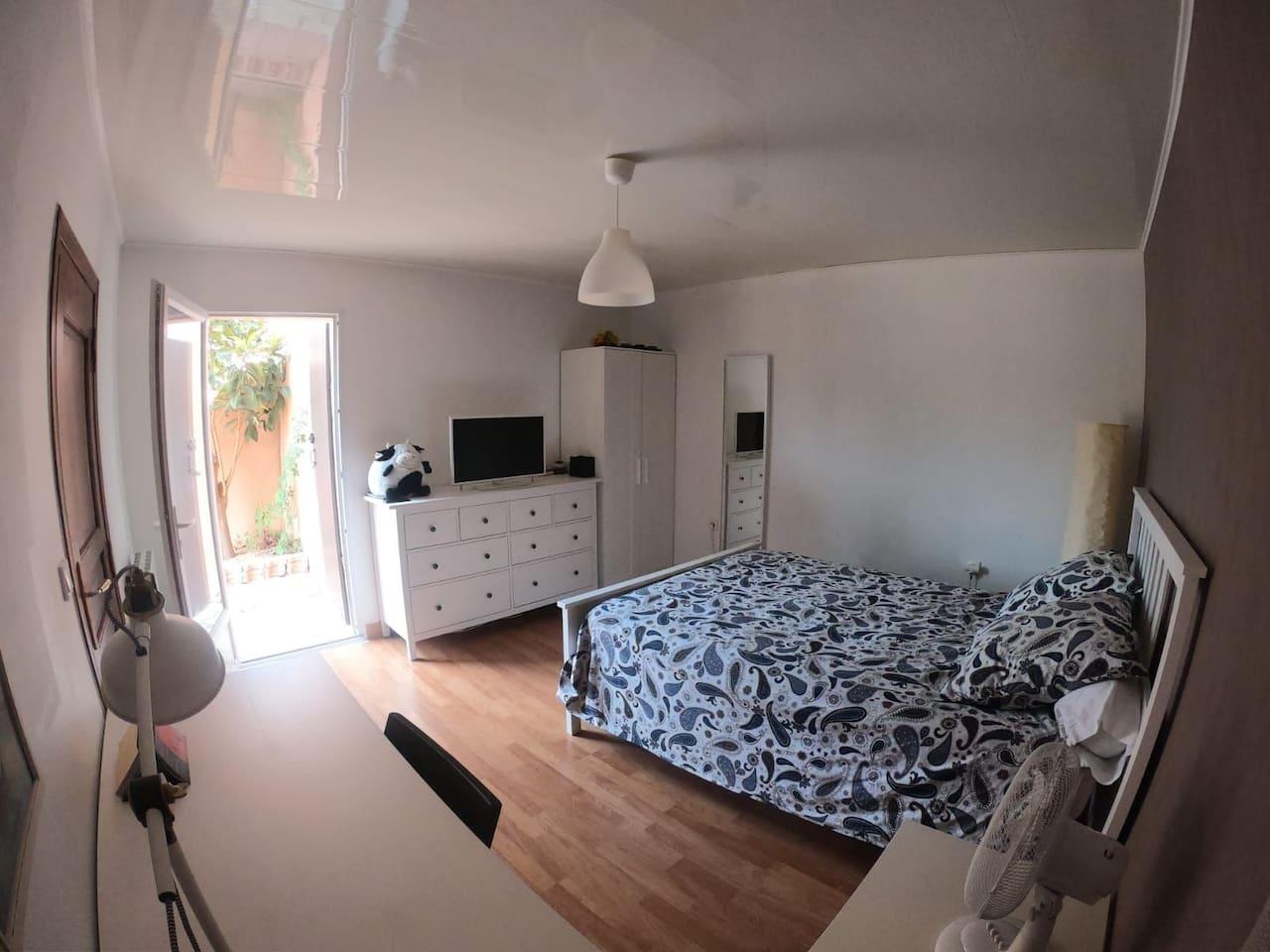 Grande chambre avec lit de 140x200, une TV, un espace bureau.