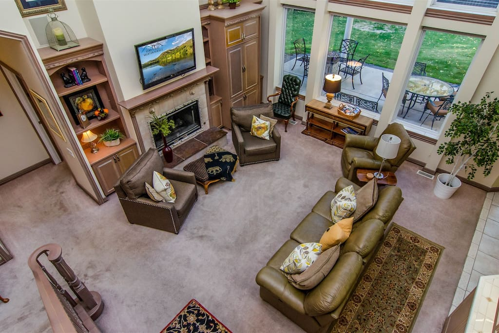 Gorgeous great room w/ 30 ft. ceiling and wall of windows, fireplace, TV & views