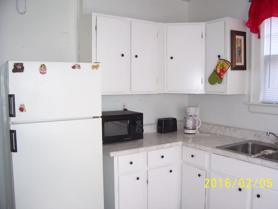 Kitchen area with fridge, microwave, toaster, and coffee machine