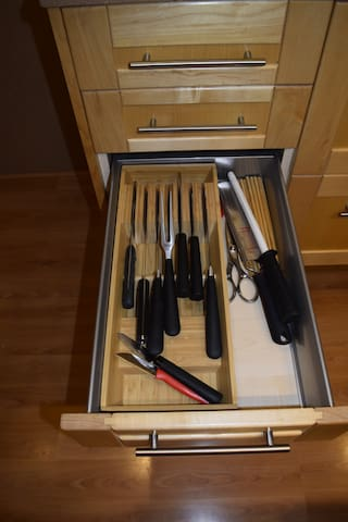 Left of stove, third drawer, various knives.