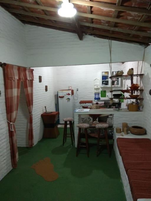 Cozinha e sala com sofá.