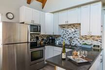 Kitchen fully stocked with cooking supplies and dining ware. Beautiful quartz countertop. Gourmet coffee maker.