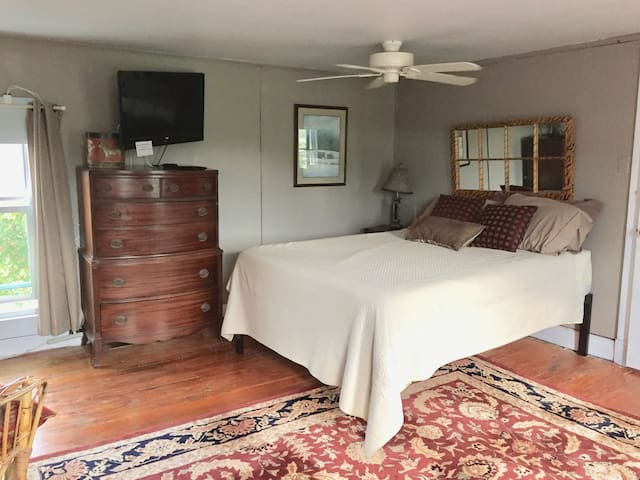 Large bedroom suite with queen size bed, tv and shared bathroom, sometimes not shared bathroom