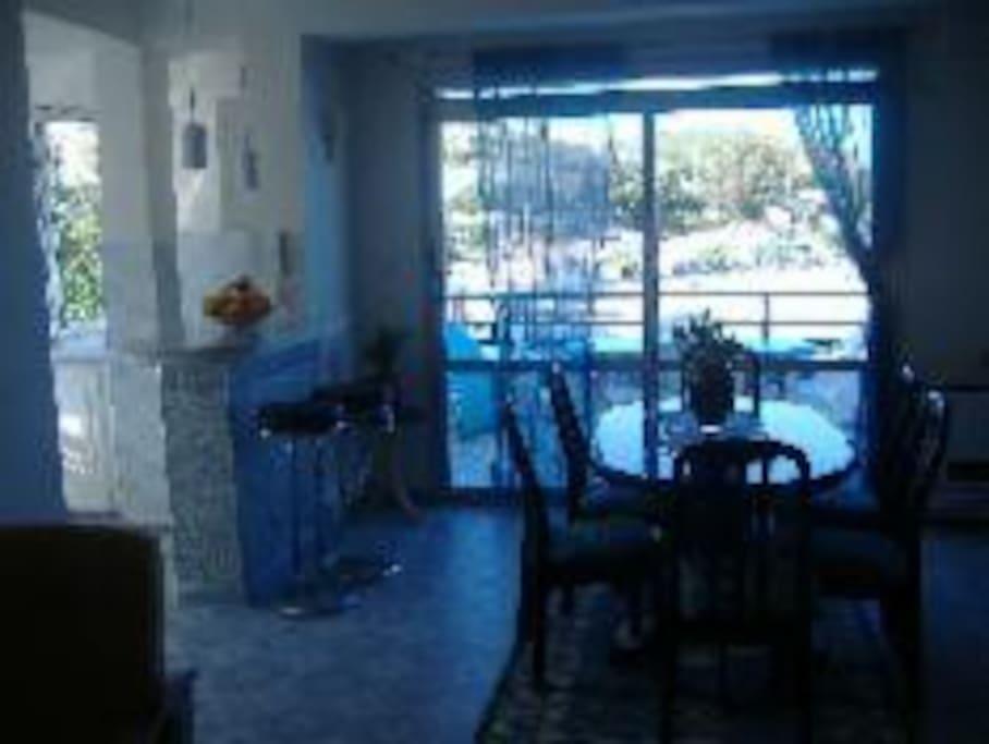 Salle à manger qui communique avec le salon et la cuisine et qui donne sur la terrasse