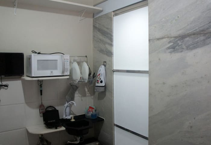 "À esquerda, a ""mini-kitchen""; à direita, a porta do banheiro (fechada)."