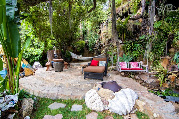 Yard/patio in front of guest house with firepit, teepee, hammock & swings over ponds with waterfalls