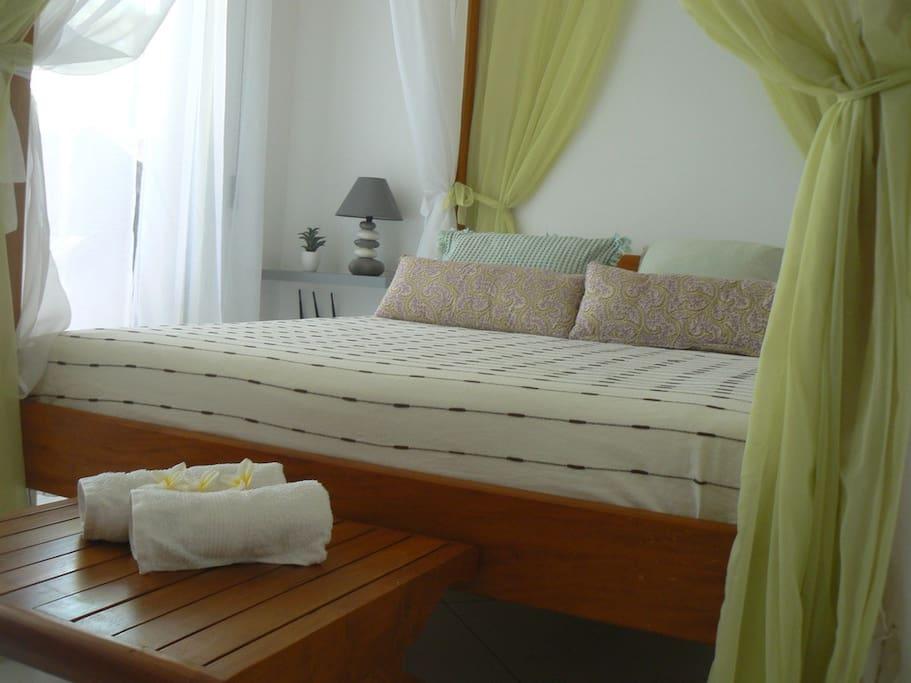 Chambre  donnant sur la terrasse -lit baldaquin .
