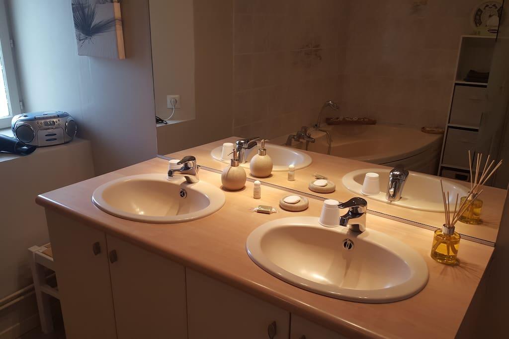 Double vasque avec sèche cheveux et serviettes de toilette.