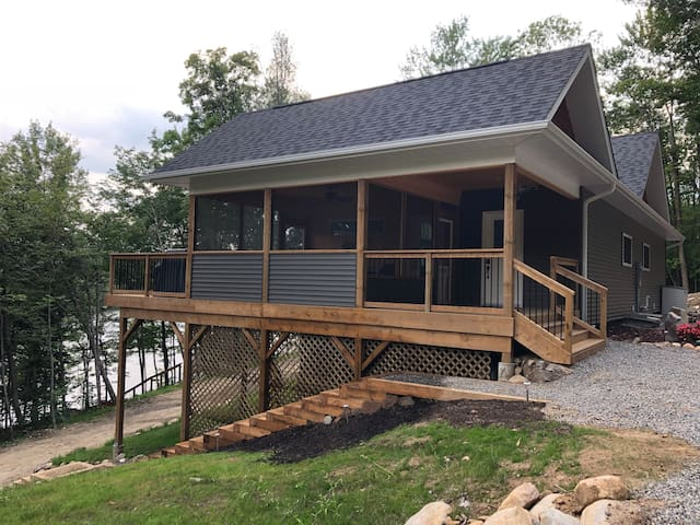 Main entrance with covered porch for unloading, screened Muskoka room, and upper deck.