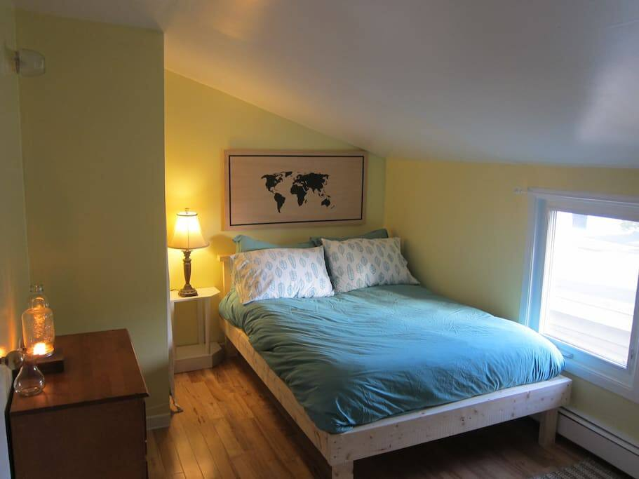The bedroom has a cozy double bed with feather duvet, dresser, closet and homemade map art!