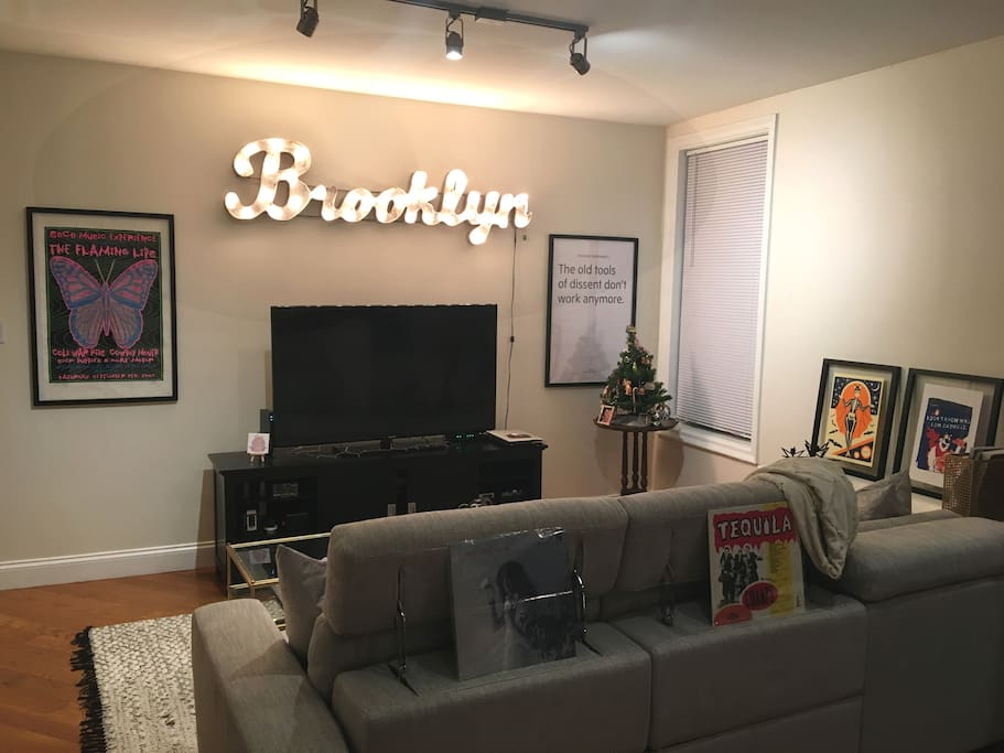 "Living room TV with Netflix and HBOGo. ""Brooklyn"" marquee light in case you forget which borough you're in."